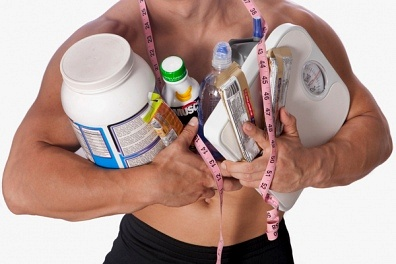 Man with a lot of bodybuilding supplements.