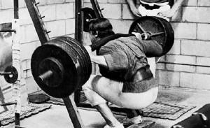 Arnold Schwarzenegger squatting deep.