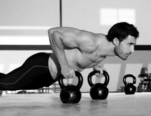 Man doing push-ups on kettlebells.