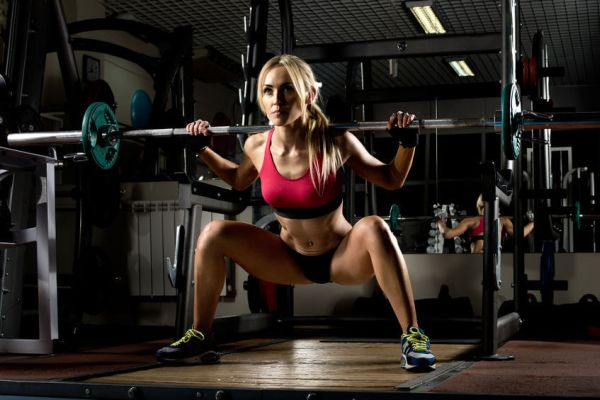 woman squatting in gym