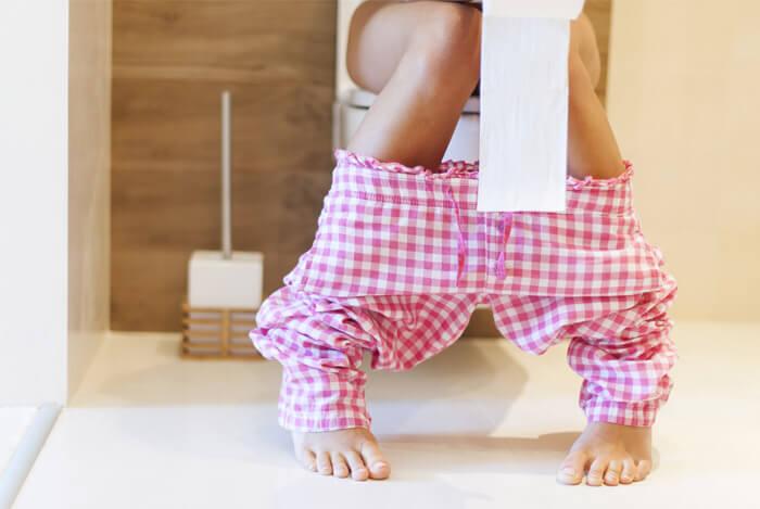 woman on toilet with diarrhea