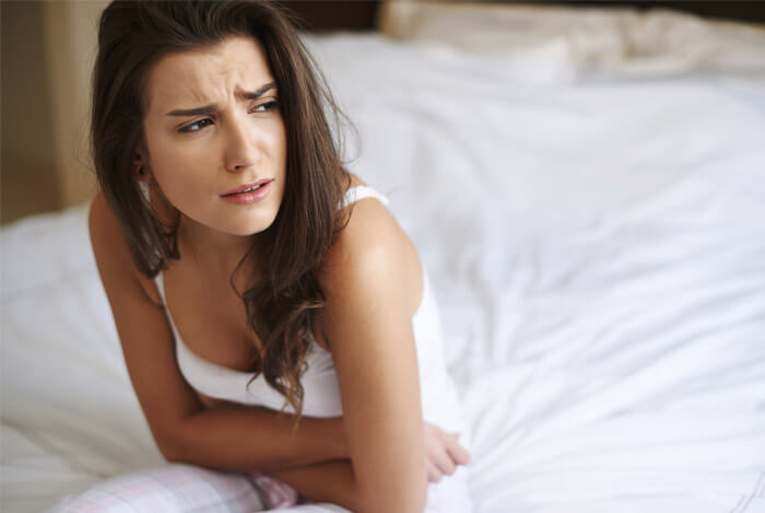 woman feeling sick on bed